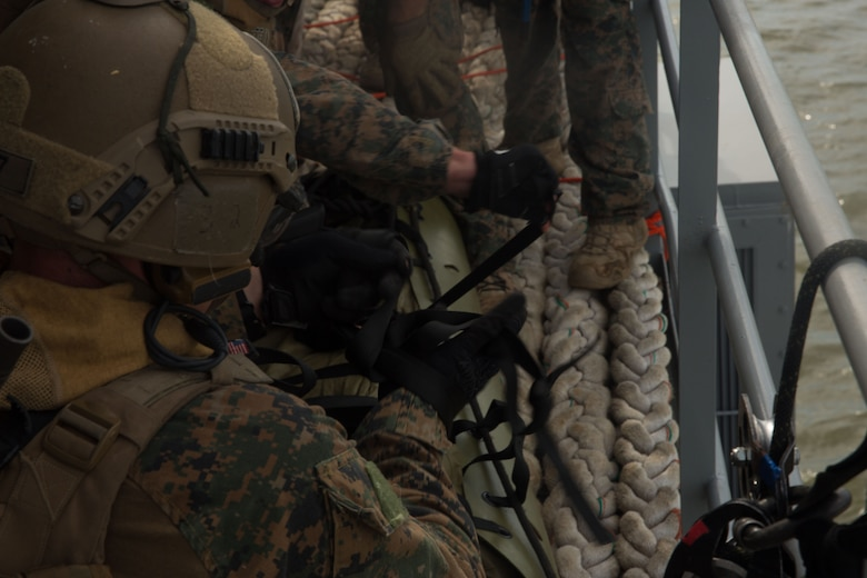 U.S. Marines with the Maritime Raid Force (MRF), 26th Marine Expeditionary Unit (MEU), tie a bowline knot around a simulated casualty during a raid as part of visit, board, search and seizure (VBSS) training at Fort Eustis, Va., Aug. 2, 2017.