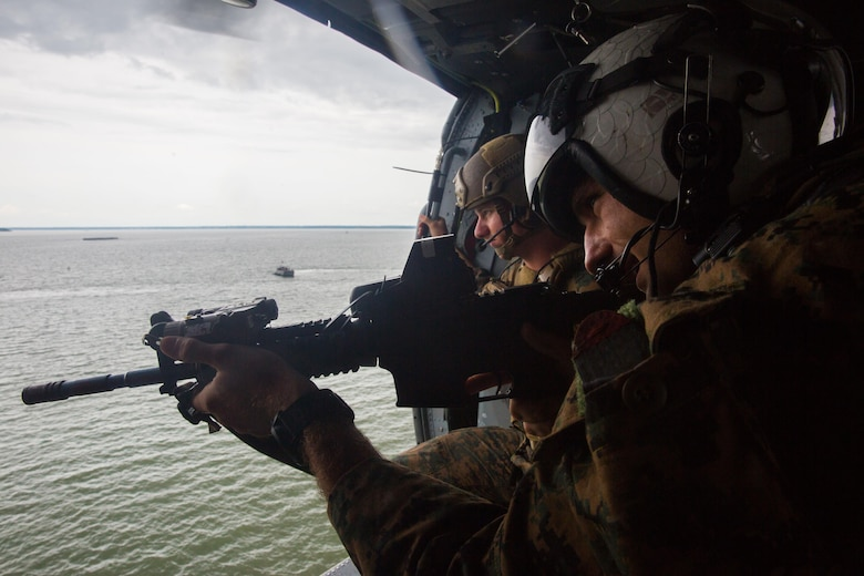U.S. Marines with the Maritime Raid Force (MRF), 26th Marine Expeditionary Unit (MEU), provide overhead security with a training M4A1 rifle during a raid as part of visit, board, search and seizure (VBSS) training at Fort Eustis, Va., Aug. 2, 2017.