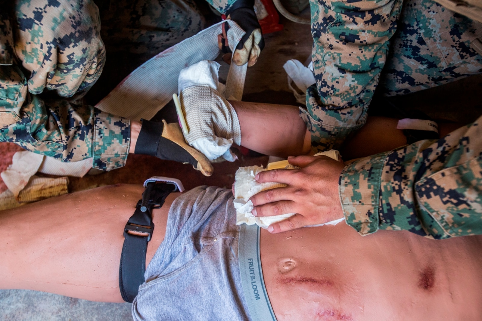 U.S. Marines treat the wounds of a simulated casualty during a field medical training exercise on Marine Corps Base Camp Pendleton, Calif., Jul. 18, 2017. The trauma manikins provide students with are not only anatomically correct but allow training on various wounds to include amputation, sucking chest wounds, fractures, gunshot wounds, abdominal eviscerations and airway compromise due to facial trauma.