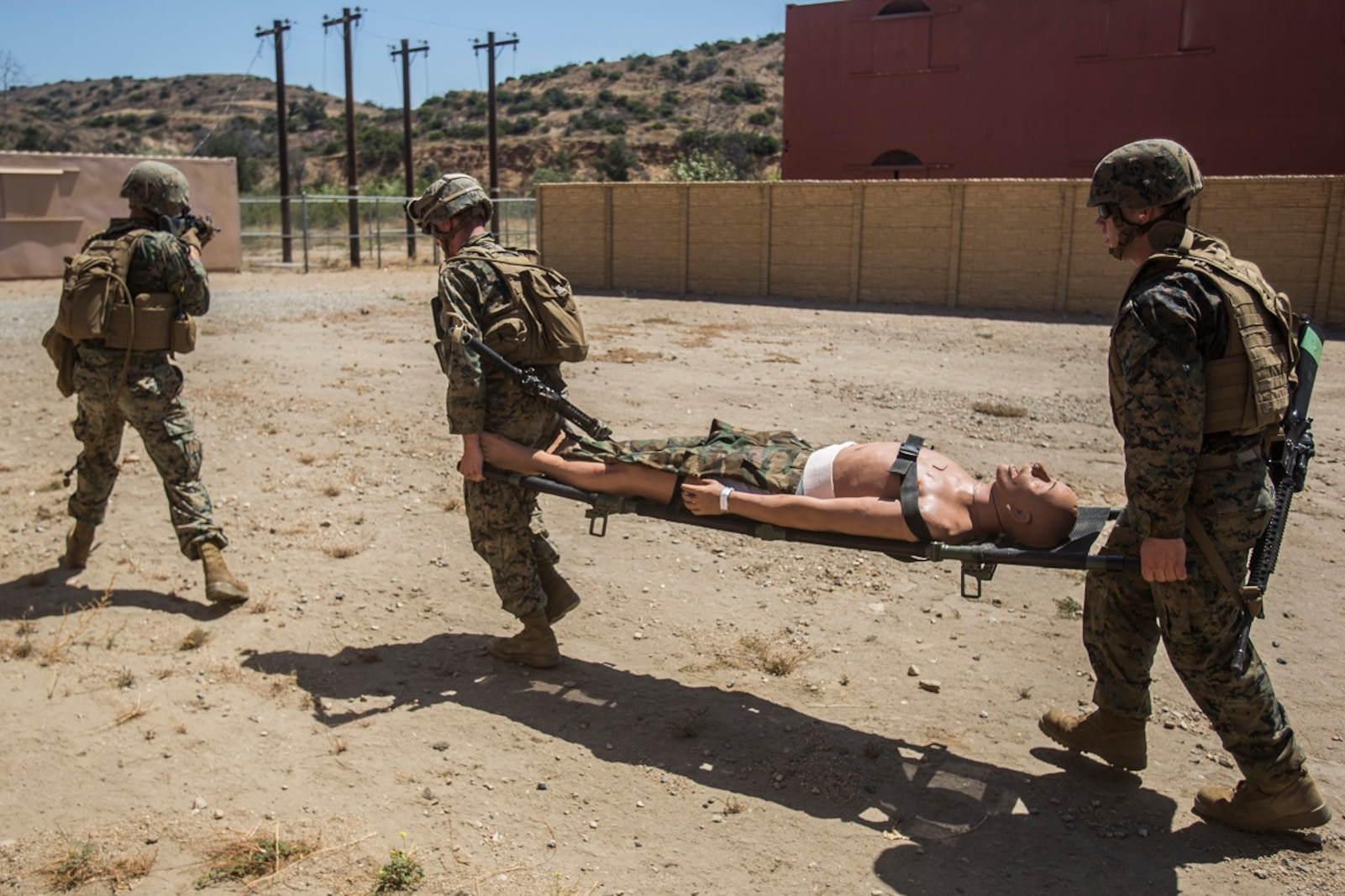 A U.S. Marine with Combat Logistics Battalion 13 provides security while a simulated casualty is transported to safety during a field medical training exercise on Marine Corps Base Camp Pendleton, Calif., Jul. 18, 2017. The Marines are placed in scenarios meant to test them not only tactically through patrolling but also establishing and securing an expedient casualty collection point, assessment, treatment and triage of all casualties, and movement of patient under fire to a landing zone.