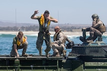 A U.S. Marine with 3rd Assault Amphibian Battalion, jumps off an Amphibious Assault Vehicle (AAV) during an annual surf qualification at Camp Pendleton, Calif., Aug. 17, 2017. The annual training included a 500 meter swim from Amphibious Assualt Vehicles (AAV)  to shore to simulate an AAV sinking in the ocean. (U.S. Marine Corps photo by Lance Cpl. Roxanna Gonzalez)