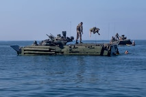 A U.S. Marine with 3rd Assault Amphibian Battalion, jumps from an Amphibious Assault Vehicle (AAV) during an annual surf qualification at Camp Pendleton, Calif., Aug. 17, 2017. The annual training included a 500 meter swim from AAVs to shore to simulate an AAV sinking in the ocean. (U.S. Marine Corps photo by Lance Cpl. Roxanna Gonzalez)