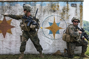 One Marine kneels by a wall while another stands and points.