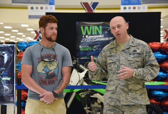 Col. Danny Davis, 81st Mission Support Group commander, delivers remarks about U.S. Army Spc. Anthony Clark, Alpha Company 1-155th infantryman, Mississippi National Guard, Biloxi, Miss., after he won a Kawasaki KXTM250F motorcycle at the Base Exchange, Aug. 19, 2017, on Keesler Air Force Base, Miss. Clark, a Biloxi native, was randomly selected from more than 16,000 entries to win the Army & Air Force Exchange Service's Monster Kawasaki Sweepstakes, which ran from April 15 to May 31. (U.S. Air Force photo by Kemberly Groue)