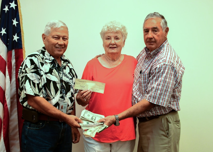 From left, Dallas Godfrey, Square and Compass Club Corn and Sausage Roast chairman, Nancy Black, Dobbins thrift shop manager, and Ron Durant, Square and Compass Club secretary, present the earnings from this year's Corn and Sausage Roast Fundraiser at Dobbins Air Reserve Base, Ga. Aug. 17, 2017. The event raised $2,004, which will go toward helping military families with unexpected expenses while a service member is deployed. (U.S. Air Force photo/Staff Sgt. Andrew Park)