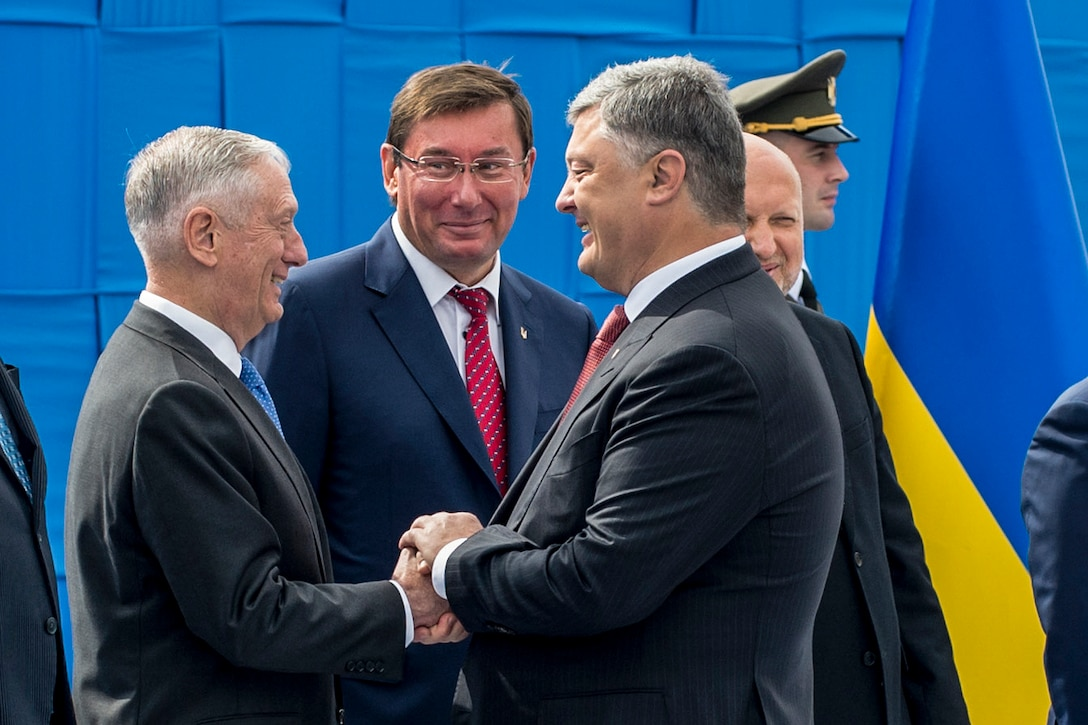 Defense Secretary Jim Mattis shakes hands with the Ukrainian president on a stage.
