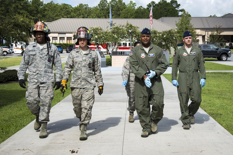 Firefighters from the 23d Civil Engineer Squadron and flight doctors from the 23d Aerospace Medical Squadron walk onto the scene during an emergency response exercise, Aug. 22, 2017, at Moody Air Force Base, Ga. The purpose of this active-shooter exercise was to inspect the recovery phase of an emergency situation while maintaining realism as members still responded as normal. (U.S. Air Force photo by Airman 1st Class Erick Requadt)