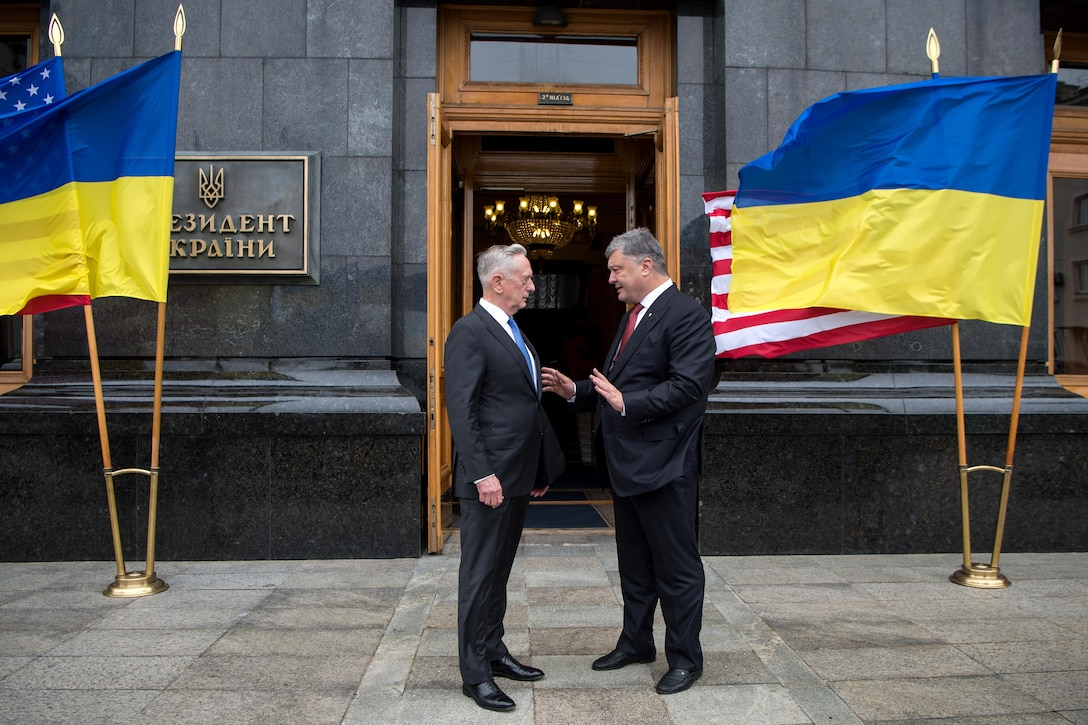 Defense Secretary Jim Mattis speaks with the Ukrainian president outside a building.
