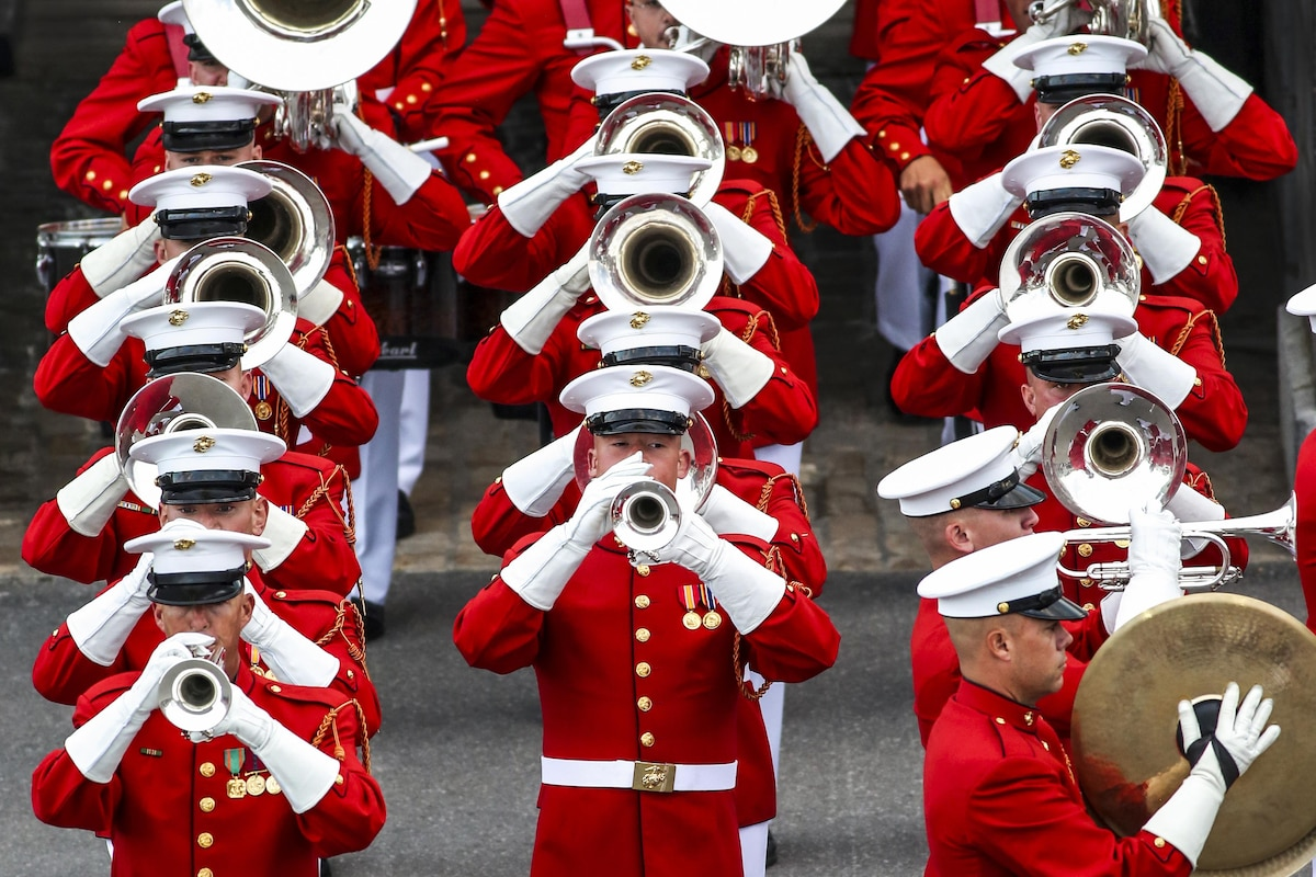 Marine Corps musicians play instruments and march in formation.