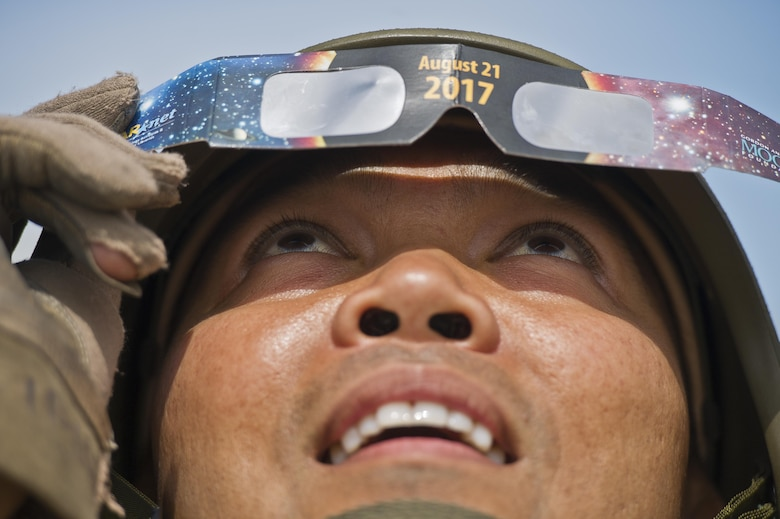 U.S. Air Force Capt. Vincent Alipio, assigned to the 349th Medical Squadron, Travis AFB, Calif., observes through his eclipse glasses as the moon passes in front of the sun during a total solar eclipse at Young Air Assault Strip, Fort McCoy, Wis., Aug. 21, 2017, while participating in exercise Patriot Warrior. More than 600 Reserve Citizen Airmen and over 10,000 soldiers, sailors, Marines and international partners converged on the state of Wisconsin to support a range of interlinked exercises including Patriot Warrior, Global Medic, CSTX, Diamond Saber, and Mortuary Affairs Exercise (MAX).  Patriot Warrior is Air Force Reserve Command's premier exercise, providing an opportunity for Reserve Citizen Airmen to train with joint and international partners in airlift, aeromedical evacuation and mobility support.  This exercise is intended to test the ability of the Air Force Reserve to provide combat-ready forces to operate in dynamic, contested environments and to sharpen Citizen Airmen's skills in supporting combatant commander requirements. ( U.S. Air Force Photo by Tech. Sgt. Efren Lopez )