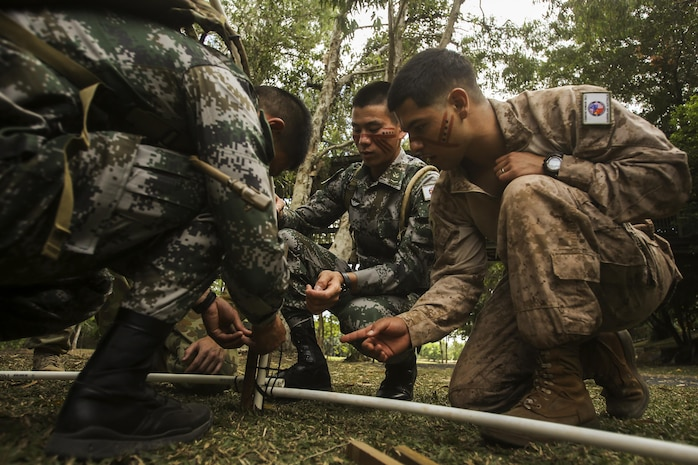 CAIRNS, Australia – U.S. Marine Cpl. Nicolas Villanueva, right, motor transportation operator, Combat Logistics Detachment, Marine Rotational Force Darwin, works with soldiers from the Chinese People's Liberation Army to build a hut during Indigenous Australian culture classes for Exercise Kowari 2017 Aug. 23, 2017. After the opening ceremony, the Soldiers and Marines also took part in some traditional activities such as boomerang throwing and tribal face painting to introduce those visiting from the US and China to Indigenous Australian culture. Kowari is an annual training activity held in Australia to reinforce trilateral military relationships, trust and co-operation between Australia, China and the United States. (U.S. Marine Corps photo by Sgt. Emmanuel Ramos)