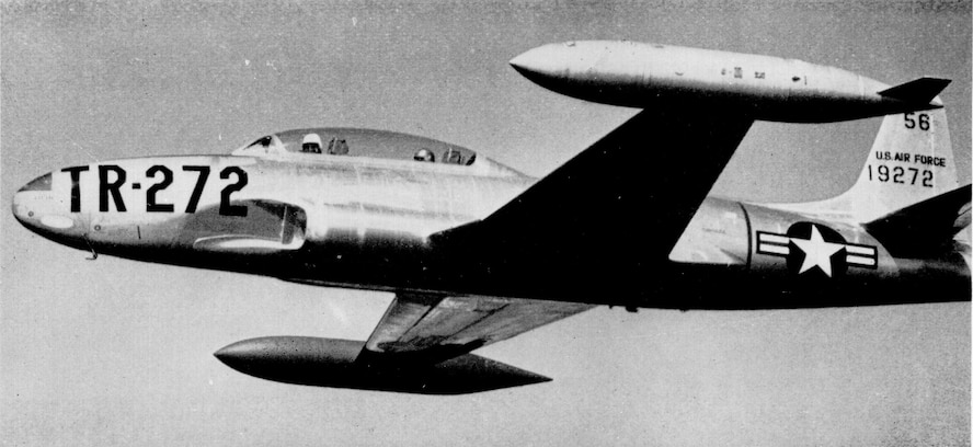 A T-33A Shooting Star shown in-flight in standard training configuration with wingtip tanks wearing natural-metal and early training command markings.
