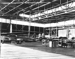A T-33A Shooting Star wearing natural-metal and large aircraft identification markings sits inside a hangar at Tinker Air Force Base, Oklahoma in this undated photo from the Tinker archives.