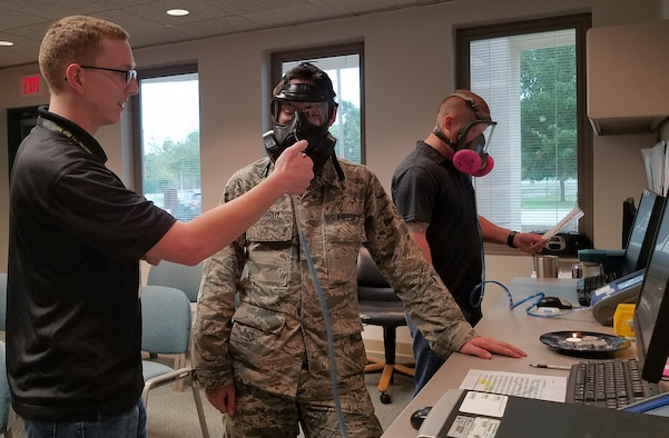 Tyler Miner of the 72nd Aerospace Medicine Squadron's Bioenvironmental Engineering Flight conducts a gas mask fit test to a military member while a civilian member is getting his industrial respirator fit tested so they will be protected from potential airborne hazards produced during their specific maintenance processes