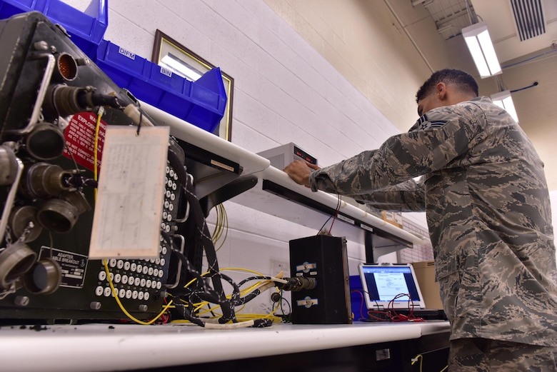 U.S. Air Force Senior Airman Christian Anthony, an electrical and environmental specialist assigned to the 509th Maintenance Squadron, connects an overhead lighting control unit onto a breakout box at Whiteman Air Force Base, Mo., Aug. 3, 2017.