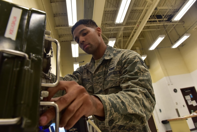 U.S. Air Force Senior Airman Christian Anthony, an electrical and environmental specialist assigned to the 509th Maintenance Squadron, grabs a breakout box to test an overhead lighting control panel at Whiteman Air Force Base, Mo., Aug. 3, 2017.