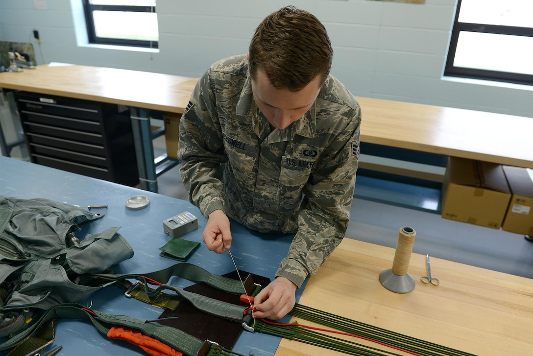 U.S. Air Force Senior Airman Thomas Cadwell, an air-crew flight equipment technician assigned to the 509th Operations Support Squadron, inspects a four-line re-lease at Whiteman Air Force Base, Mo., Aug. 21, 2017. The four-line release is used after the pilot has ejected and needs to steer the parachute to keep it from landing in an unsafe area.