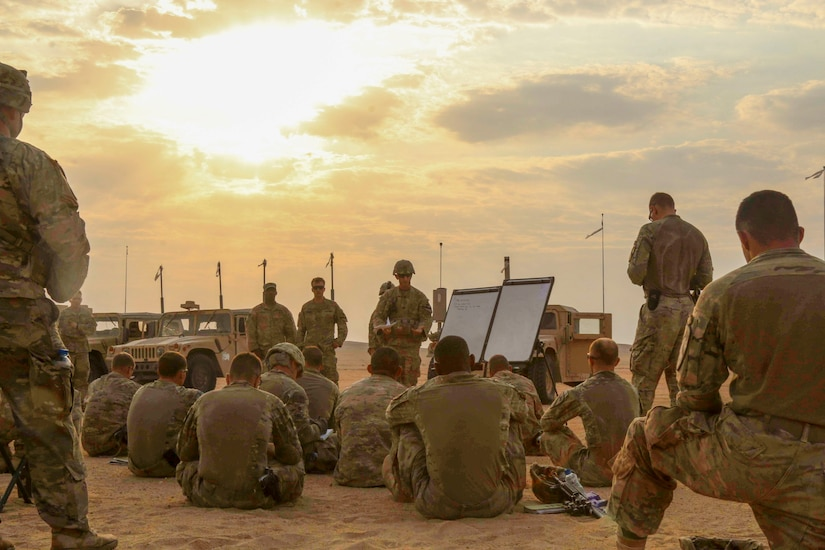 The Soldiers and leaders of Bravo Company, 3rd Battalion, 8th Cavalry Regiment, 3rd Armored Brigade Combat Team, 1st Cavalry Division gather around for the after-action review following their three-day company situational training exercise at Udairi Range Complex in Kuwait Aug. 12, 2017. The brigade organized this training event to sustain the readiness of the combined arms battalions. (U.S. Army photo by Staff Sgt. Leah R. Kilpatrick)