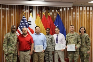 Group facing viewer, some holding certificates