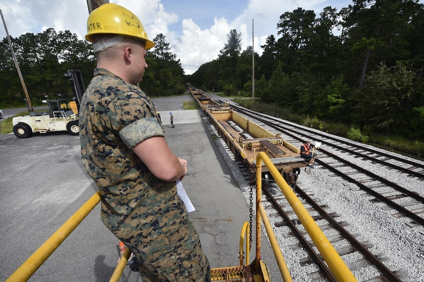 U.S. Marine Cpl. Melvin Willis, Naval Munitions Command Marine Corps Liaison Office member, waits for the arrival of a train transporting munitions during a container download operation at the Joint Base Charleston Weapons Station, S.C., Aug. 21. Marines attached to the NMC's Marine Corps Liaison Office are responsible for inspecting munitions containers to ensure they are receiving safe quality items during the download. These Marines work alongside NMC civilians and members of the U.S. Air Force 628th Logistics Readiness Squadron to prepare them for transport to their final destination.