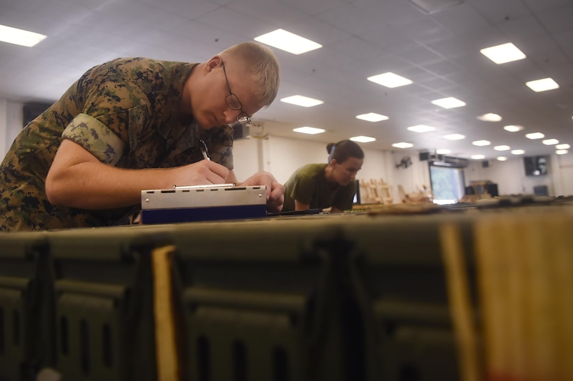 U.S. Marine Sgt. Nathan Smothers, Naval Munitions Command Marine Corps Liaison Office member, records inventory information during a munitions inspection at the Joint Base Charleston Weapons Station, S.C., Aug. 23. Marines attached to the NMC's Marine Corps Liaison Office are responsible for inspecting munitions containers to ensure they are receiving safe quality items during the download. These Marines work alongside NMC civilians and members of the U.S. Air Force 628th Logistics Readiness Squadron to prepare them for transport to their final destination.