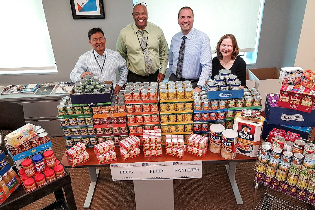 Four people stand behind a table display of nonperishable food items.