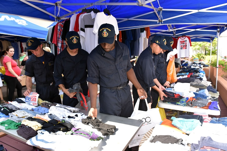 SINGAPORE (Aug. 23, 2017) Sailors from the USS John S. McCain (DDG 56) are assisted by volunteers in looking for personal items donated by community members of the Singapore Area Coordinator. The McCain sustained significant damage following a collision with the merchant vessel Alnic MC while underway east of the Strait of Malacca and Singapore on Aug. 21, 2017.