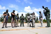 Airmen with the 319th Security Forces Squadron, U.S. Customs and Border Protection agents, and officers with the Grand Forks Sheriff's Department gather to discuss a plan of entry during a training exercise at Carl Ben Eielson Elementary School Aug. 9, 2017, on Grand Forks Air Force Base, N.D. The USCBP led the three-day event, providing classroom and hands-on training dealing with a variety of active-shooter scenarios.  (U.S. Air Force photo by Airman 1st Class Elora J. Martinez)