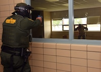 A U.S. Customs and Border Protection agent apprehends his target through a classroom window during active-shooter training at Carl Ben Eielson Elementary School Aug. 9, 2017, on Grand Forks Air Force Base, N.D. Those who participated in the training were given simulation weapons that shot rounds filled with washable paint. (U.S. Air Force photo by Airman 1st Class Elora J. Martinez)