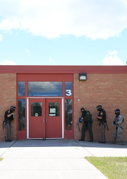 An Airman with the 319th Security Forces Squadron, far right, U.S. Customs and Border Protection agent, and officers with the Grand Forks Sheriff's Department form up outside of Carl Ben Eielson Elementary School in preparation to enter an active-shooter scenario Aug. 10, 2017, on Grand Forks Air Force Base. The training exercise was held to allow the members to practice room clearing procedures, rear security and communication in order to apprehend potential shooters. (U.S. Air Force photo by Airman 1st Class Elora J. Martinez)