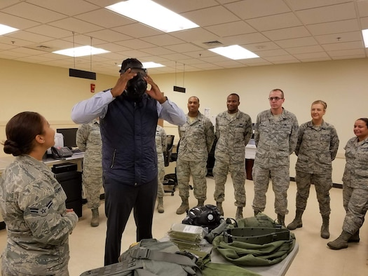 Juston White, 22nd Logistics Readiness Squadron honorary commander, tries on a gas mask during an immersion tour, Nov. 17, 2016, at McConnell Air Force Base, Kan. White was selected as an honorary commander because he's the executive director of the Boys and Girls Clubs of South Central Kansas and a board member of the Child Advocacy Center of Sedgwick County. (Courtesy photo)