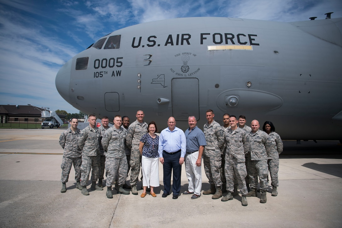 """John Levitow Jr., center, along with his cousin, Tara Bufis and her husband, James, pose with Levitow Award winners in front of the """"Spirit of Sgt. John Levitow,"""" New York Air National Guard Globemaster III during a tour of Joint Base McGuire-Dix-Lakehurst, N.J., Aug 24, 2017. Levitow Jr. spoke during the J MDL Airman Leadership School graduation of Troop 17F on his father's messages for the troops. (U.S. Air Force photo by Senior Airman Lauren Russell)"""