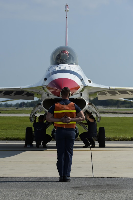 A member of the U.S.A.F. Thunderbirds marshals an F-16 Fighting Falcon Aug. 25, 2017, during the Thunder Over Dover Open House Family Day at Dover Air Force Base, Del. Lt. Col. Kevin Walsh, Thunderbirds operations officer, flew the No. 7 jet, taking Andrew Jackson, radio host for 88.7 The Bridge, on a media flight above Delaware. (U.S. Air Force photo by Staff Sgt. Aaron J. Jenne)