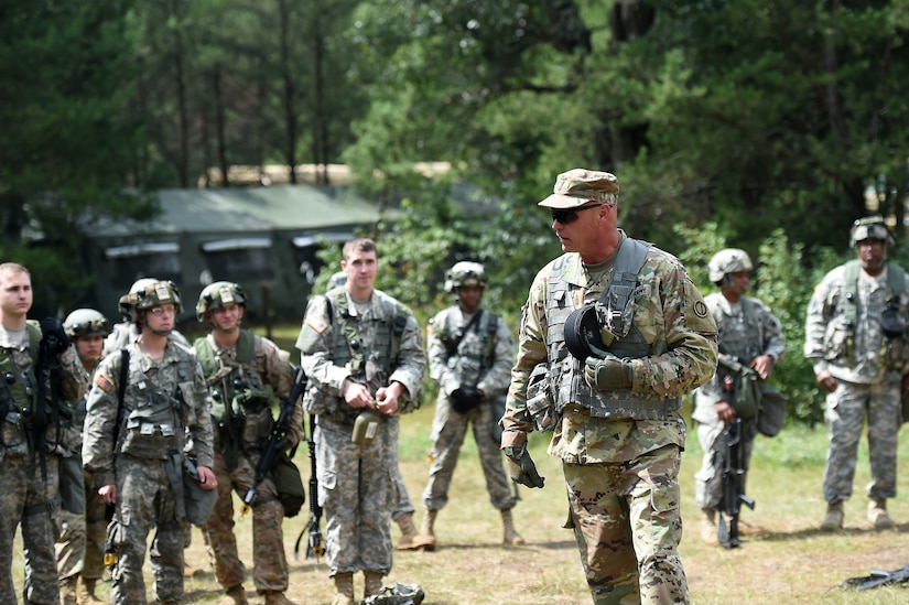 Army Reserve Chief Warrant Officer 5 Eric Nordy, left, Command Chief Warrant Officer, 85th Support Command, speaks with Soldiers from the 360th Chemical Company after a simulated base attack during Combat Support Training Exercise 86-17-02 at Fort McCoy, Wisconsin, from August 5 – 25, 2017.