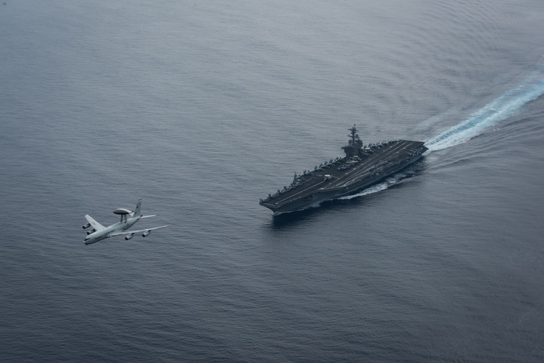 (Aug. 21, 2017) A U.S. Air Force E-3 Sentry airborne warning and control system assigned to Air Combat Command at Tinker Air Force Base flies over the aircraft carrier USS Theodore Roosevelt (CVN 71). Theodore Roosevelt is underway conducting a composite training unit exercise (COMPTUEX) with its carrier strike group in preparation for an upcoming deployment. COMPTUEX tests a carrier strike group's mission-readiness and ability to perform as an integrated unit through simulated real-world scenarios. (U.S. Navy photo by Mass Communication Specialist 3rd Class Anthony J. Rivera)