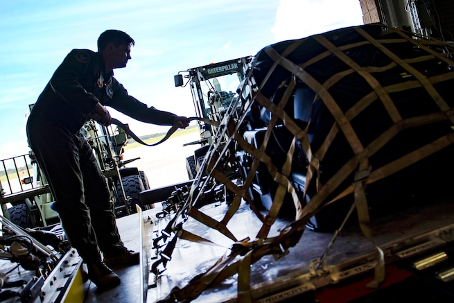 Air Force Staff Sgt. Todd Johnson secures a pallet of equipment in preparation for rescue operations.