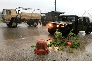 Three Texas Army National Guard vehicles patrol a street for damage.