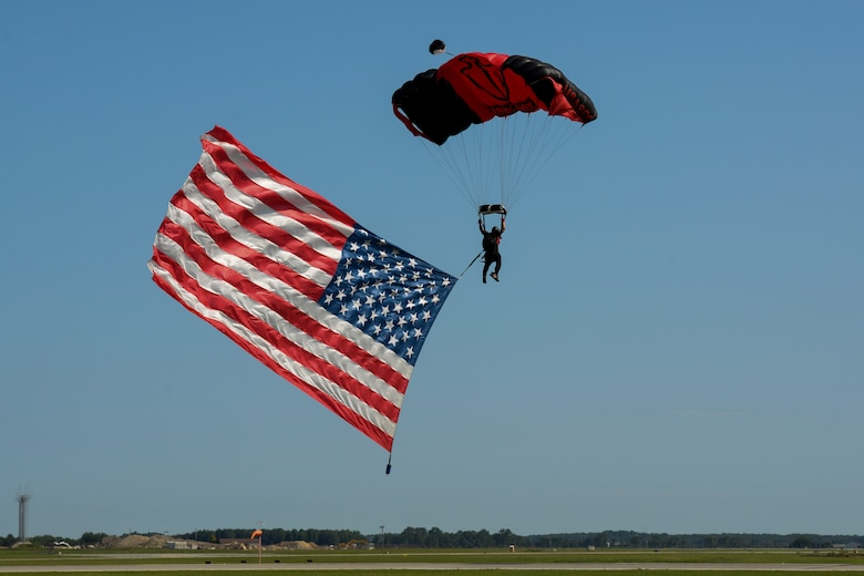 A member of the Black Daggers adjusts his parachute to land while towing the American flag during the Thunder Over Dover Open House opening ceremony Aug. 26, 2017, at Dover Air Force Base, Del.  The Black Daggers are the U.S. Army Special Operations Command's parachute demonstration team. (U.S. Air Force photo by Staff Sgt. Aaron J. Jenne)