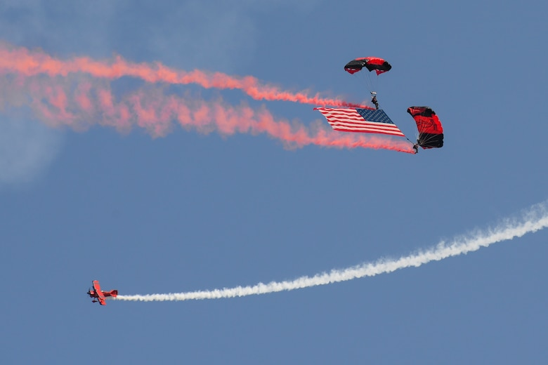 Members of the Black Daggers parachute with the American flag while ChefPitts flies in a corkscrew pattern around them Aug. 26, 2017, during the Thunder Over Dover Open House at Dover Air Force Base, Del. The Black Daggers are the U.S. Army Special Operations Command's parachute demonstration team. (U.S. Air Force photo by Staff Sgt. Aaron J. Jenne)