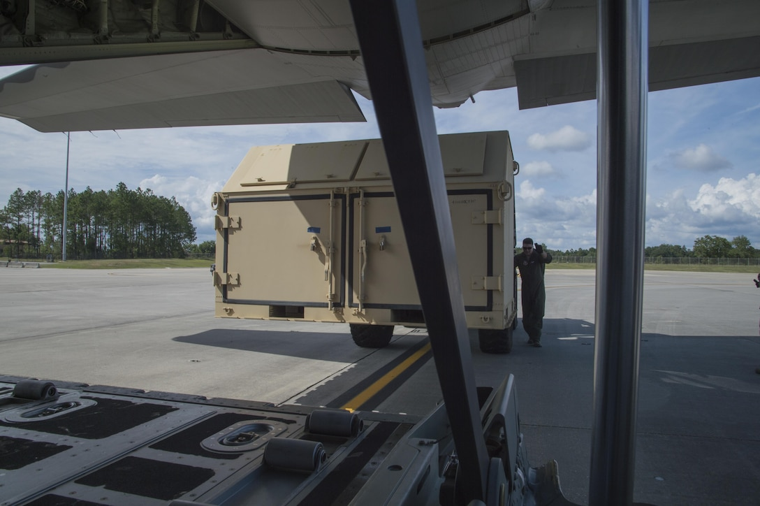 An U.S. Air Force member from the 71st Rescue Squadron guides a forklift carrying a container of equipment in to a HC-130J Combat King II traveling to Texas in preparation of possible hurricane relief support August 26, 2017, at Moody Air Force Base, Ga.