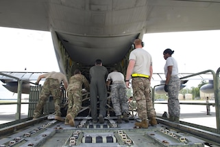 Airmen push a storage container onto a HC-130J Combat King II aircraft.
