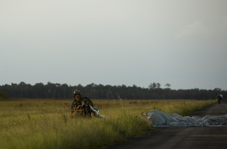 A U.S. Marine with the Maritime Raid Force (MRF), 26th Marine Expeditionary Unit (MEU), carries a Multi-Mission Parachute System during static line jump training at Camp Lejeune, N.C., Aug.15, 2017.