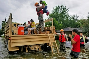 A soldier lifts a child onto a rescue vehicle in flood waters while others look on.