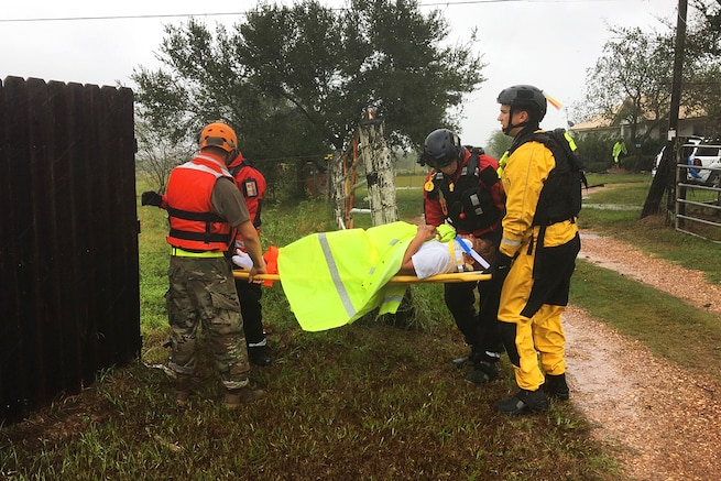 Texas National Guardsmen work with emergency responders by evacuating a resident on a stretcher.