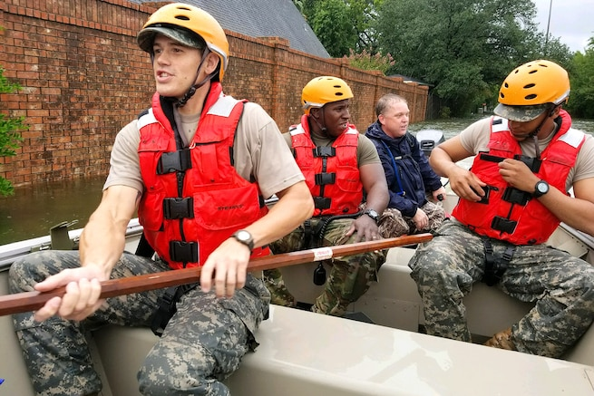 Texas National Guardsmen assist residents affected by flooding caused by Hurricane Harvey in Houston.