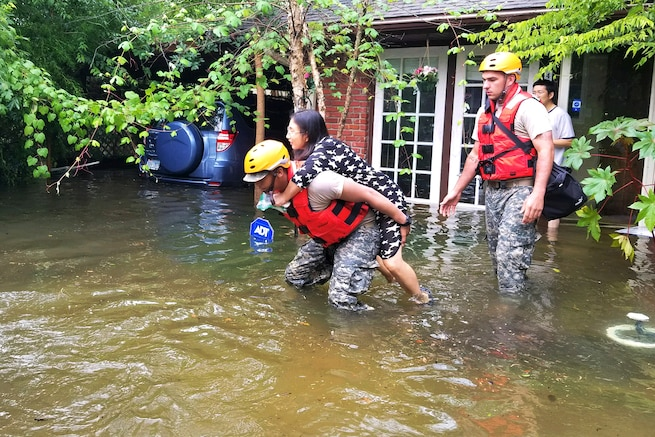 A Texas National Guardsman carry's a residents from her home affected by flooding caused by Hurricane Harvey.