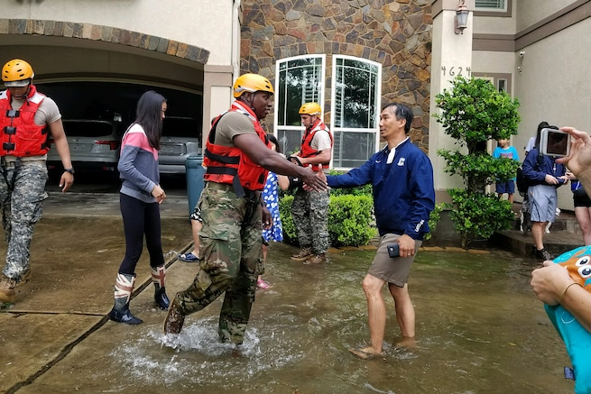 A Texas National Guardsman shakes hands with a resident after assisting his family.