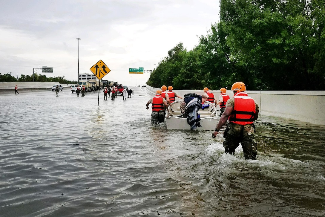 Texas National Guardsmen pull a boat with a resident displaced by flooding.