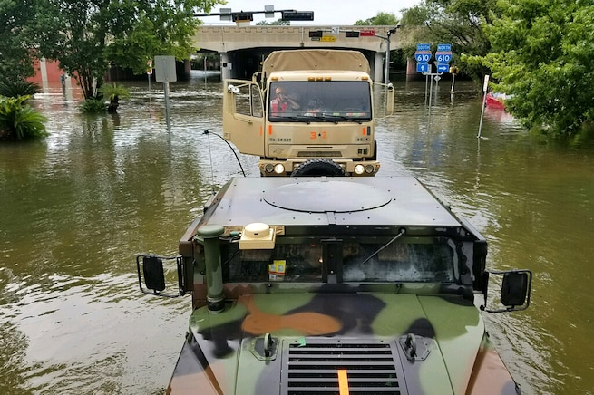 Texas National Guardsmen drive military vehicles down flooded streets while searching for stranded residents.