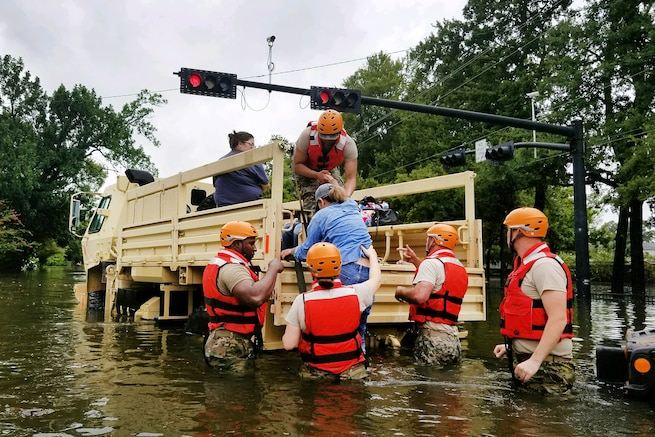 Texas National Guardsmen assist residents onto a military vehicle.